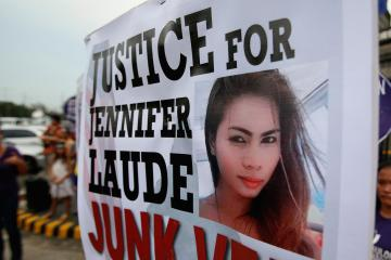 Protesters display a placard with a picture of Laude during a rally in Manila