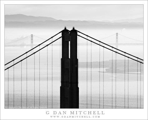 Golden Gate and Bay Bridges, Morning Haze - Black and white photograph of Golden Gate Bridge north tower, the San Francisco-Oakland Bay Bridge, and the East Bay Hills in morning haze.