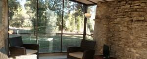 La véranda traversante avec vue sur la forêt, les montagnes et la piscine