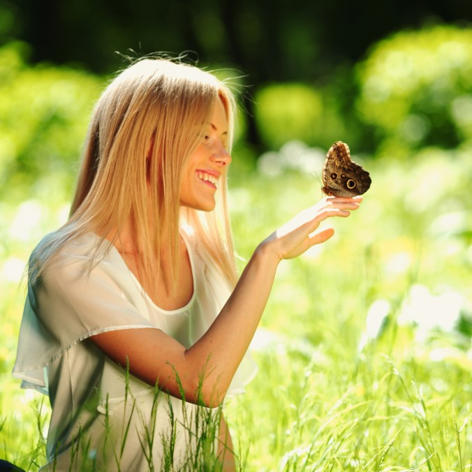 Blond woman sitting in a field of grass. She is smiling peacefully and looks at a butterfly that sits on her hand.