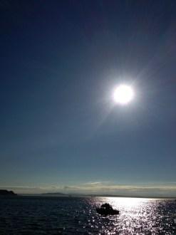 Silhouette of a boat on the glistening sea.