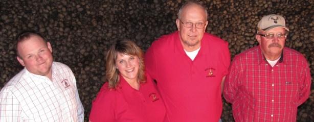 Weston Walker, Tricia (Walker) Hill, Bill Walker and John Walker standing in a potato storage cellar at Gold Dust Potato Processors.