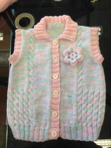 childs gilet with contrasting border and flower