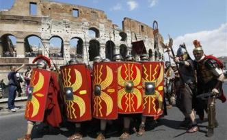 Members of Gruppo Storico Romano dressed as centurions march past ancient Colosseum in Rome