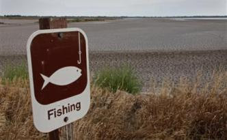 A fishing sign in at one of the dry pools at the Quivira National Wildlife Refuge in Hudson