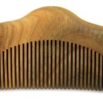 Photo of a curved wooden beard comb.