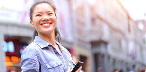 young asian woman using her smart phone in the street