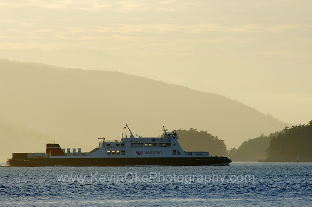 The freight ferry operated by Seaspan heads towards the lower mainland in front of Salt Spring Island and Prevost Island. The photograph is shot from Roe Islet at Roesland on North Pender Island, Gulf Islands, BCSeaspan ferry heading towards Richmond, British Columbia