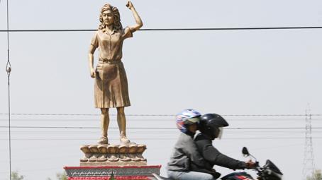 Pengendara melintas di depan patung pahlawan buruh Marsinah yang baru dibangun kembali setelah patung yang lama rusak dan hancur akibat ditabrak mobil truk, di Desa Nglundo, Sukomoro, Nganjuk, Jawa Timur, Selasa (23/9). Sejumlah Organisasi dan elemen serikat buruh Jatim mengusulkan kepada Pemerintah Provinsi Jawa Timur untuk membangun Monumen Pahlawan Buruh Marsinah di areal makam Marsinah sebagai bentuk penghormatan atas perjuangan Marsinah yang memperjuangkan hak-hak dan nasib buruh. ANTARA FOTO/Rudi Mulya/ed/mes/14