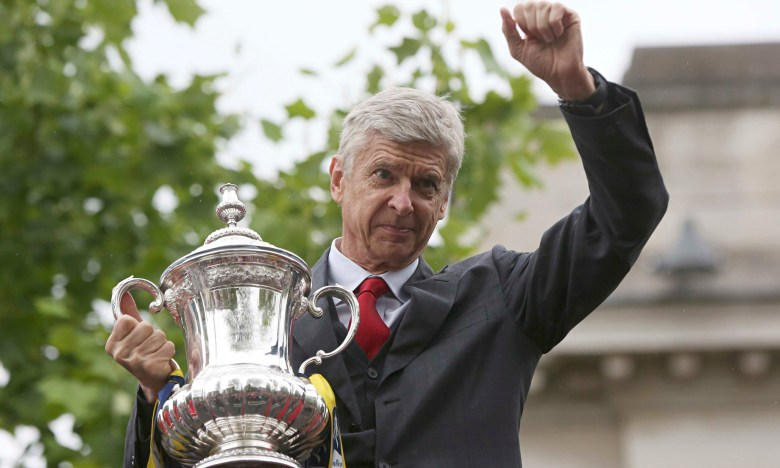 The Arsenal manager Arsene Wenger holds the FA Cup during Sunday's victory parade in north London.