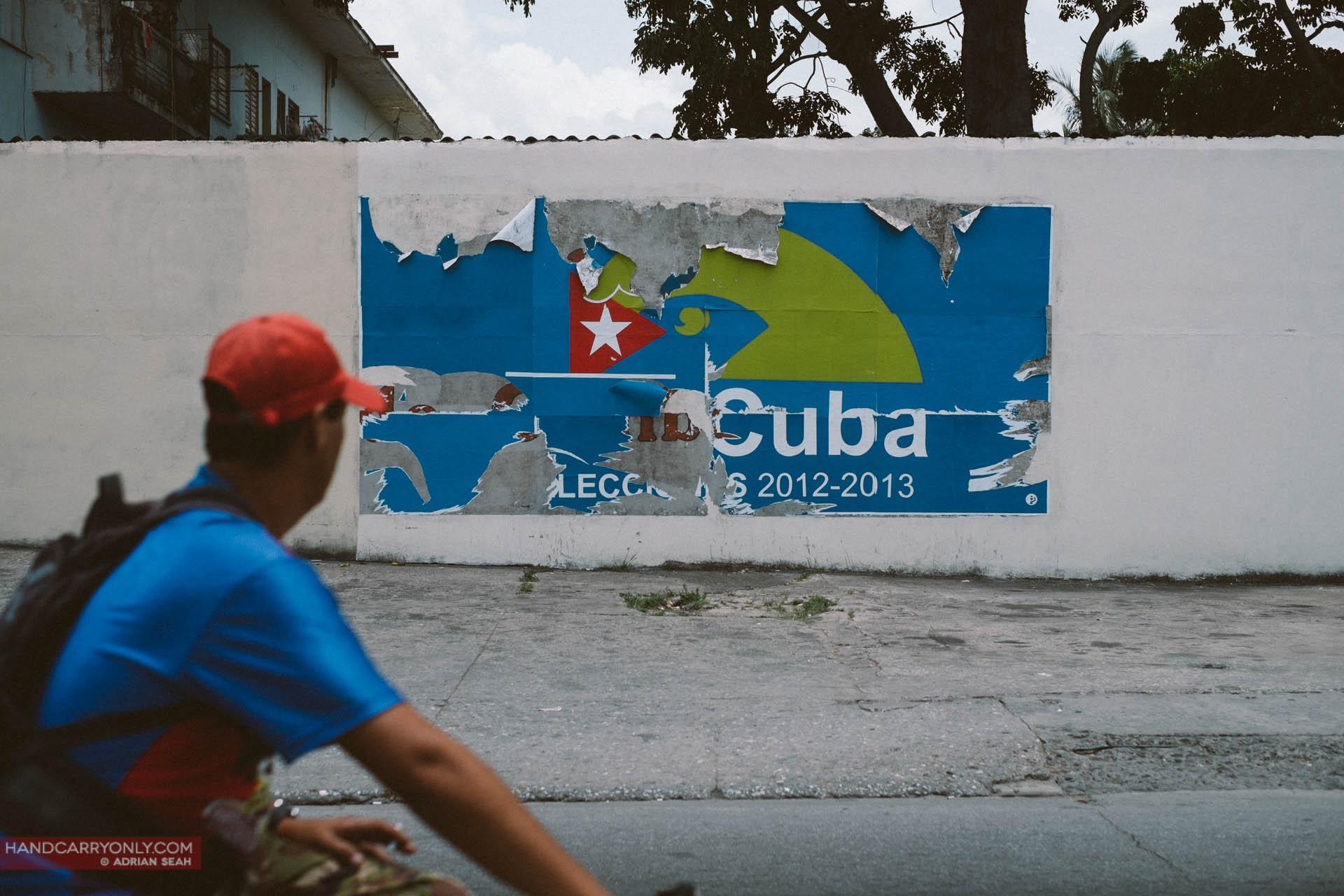 man cycling past crumbling cuban sign
