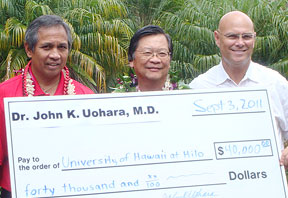 Three men with giant check