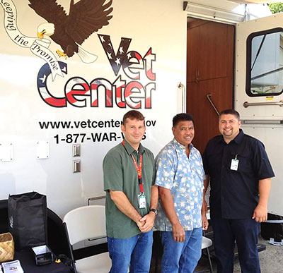 Three men in front of the Mobile Vet Center truck