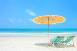 Blue sea and white sand beach with beach chairs