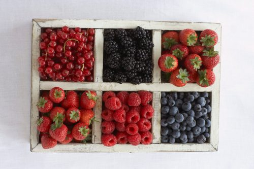 Assorted berry fruits in container, view from above