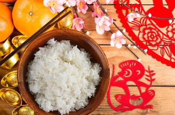 wood table with oranges, cherry blossoms, red monkey crafts and bowl of white rice with chop sticks