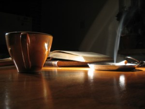 coffee lit cigarette and book on dark background to signify early morning