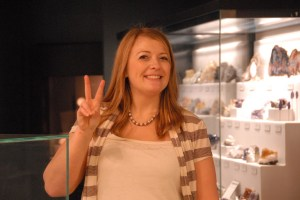 donna giving peace sign in from of mineral gallery display