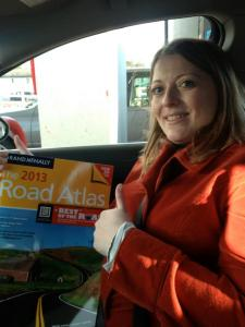 donna talarico in car holding atlas with thumbs up