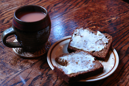 sliced & buttered banana ginger parkin on a plate with a mug of tea