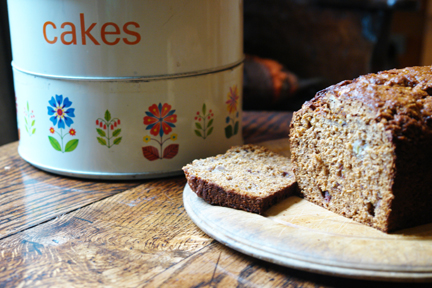 sliced banana ginger parkin on a vintage wooden chopping board alongside a vintage tiered cake tin