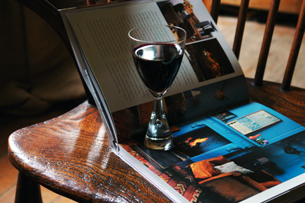 """Comforts of Home"" book open with glass of wine"
