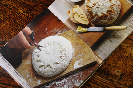 "image of an unbaked loaf being slashed with scissors to decorate in the ""How to Make Bread"" book"