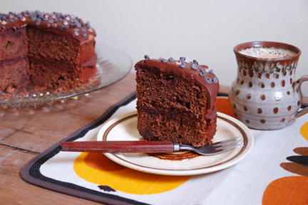 slice of mocha fudge cake on a plate with mug of coffee