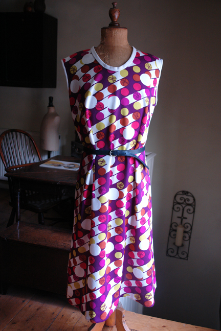 full front view of vintage 1960s/70s sleeveless patterned polyester dress with thin belt