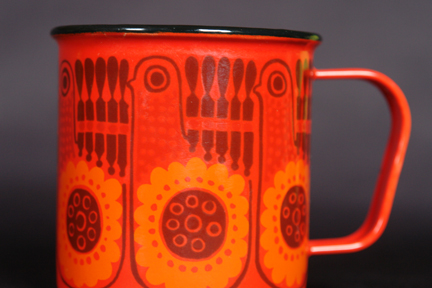 detailed view of red, vintage Finel enamel mug decorated with repeating bird pattern