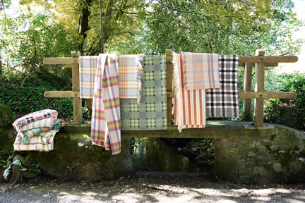 three vintage Welsh wool blankets hanging from the wooden handrail of a humpback bridge