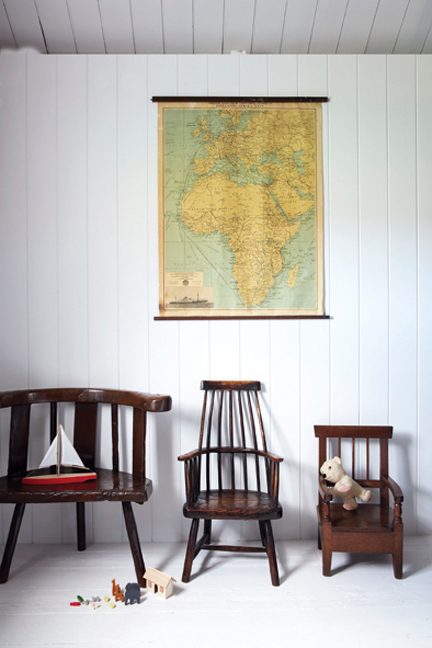 three antique Welsh country chairs under a vintage wall map