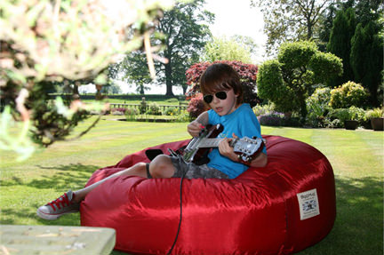 young boywearing sunglasses & playing an electric guitar sitting on a shiny red beanbag in the garden