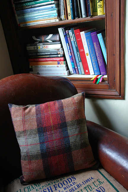 Lois scatter cushion in orange plaid from made.com on a vintage leather club chair