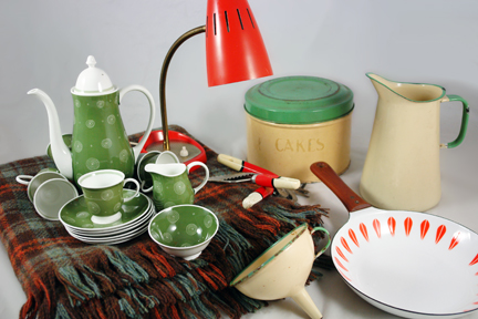 collection of recently acquired H is for Home shop stock including a Suzie Cooper coffee set, Cathrineholm Lotus frying pan, Tala cake tin, orange goose necked desk lamp and checked picnic blanket