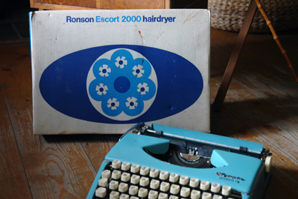 "vintage blue Olympia ""Splendid 99"" typewriter with boxed Ronson ""Escort 2000"" hairdryer in the background"