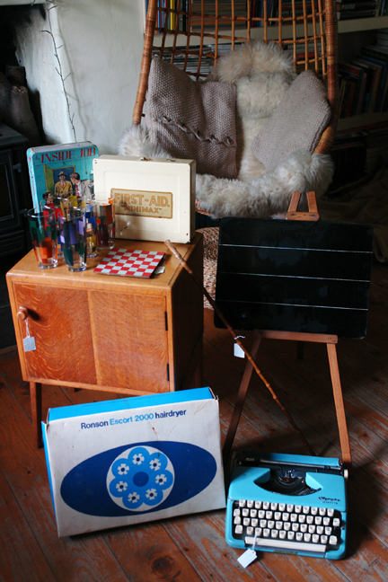 "group of vintage items including wooden bedside cabinet, blue Olympia ""Splendid 99"" typewriter, boxed Ronson ""Escort 2000"" hairdryer, vintage ""mini-max"" first aid tin, writing slate, blackboard on an easel, vintage 1950s drinking glasses and chequered pot stand"