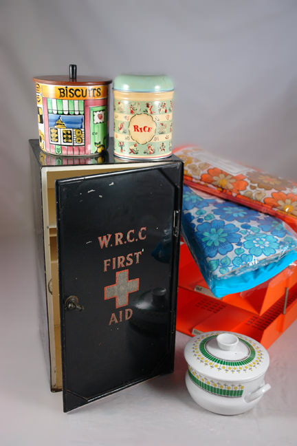 "selection of vintage homewares soon to be for sale in the H is for Home shop including large tin first aid box; orange, 3-tier filing tray; ceramic Gie Gantofta rice jar; Worcester Ware rice storage tin; Rorstrand Pottery ""Wasa"" lidded bowl; pair of 1970s Bri-Nylon floral bedding sets"