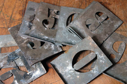 small pile of vintage metal number stencils