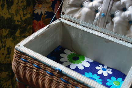 interior of a  vintage white painted wicker sewing box on legs with blue lid