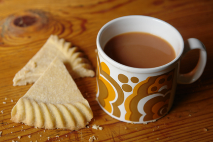 freshly cooked homemade Scottish shortbread cut into petticoat tails with a mug of tea