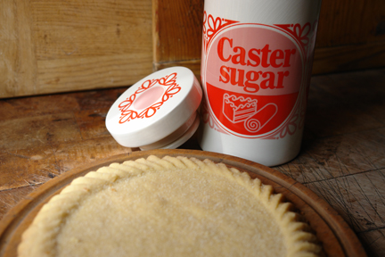 reshly cooked homemade Scottish shortbread round with vintage Lord Nelson Pottery caster sugar storage jar