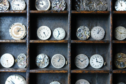 collection of vintage watch faces in a vintage printer's tray