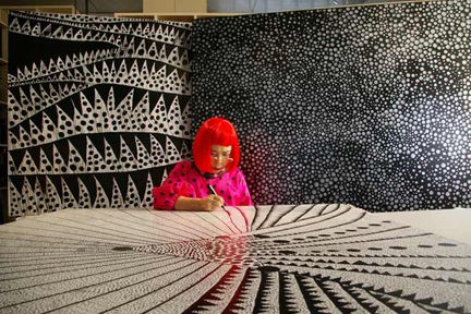 Yayoi Kusama surrounded by a selection of her paintings