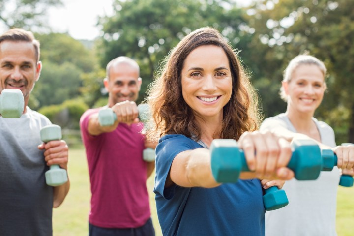 Mature people in training session of aerobics using dumbbells at park. Happy man and smiling woman practicing fitness together outdoor. Portrait of mature woman doing exercise with other people in background.