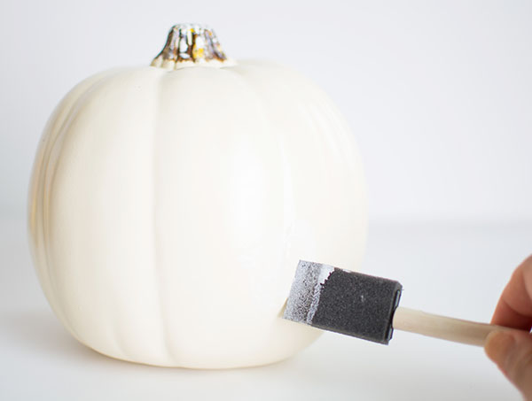 Applying Mod Podge to pumpkin