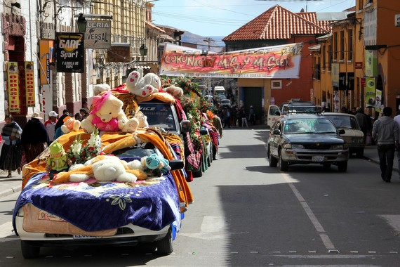 Processional of cars rounding out the parade Potosi Bolivia