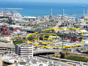 אזור תל אבו הואם במפרץ חיפה כפי שצולם בשנת 2011. שטח התל מסומן בצהוב. על המקום הגבוה בתל, נמצא היום מבנה חברת החשמל. חפירות שנים 2002/2001, התנהלו במקום בו עובר עכשיו הגשר מצפון לתל. בחפירה נחפרו הריבועים שעליהם נבנו לאחר מכן עמודי הגשר. הגשר שבתחתית התמונה הוא גשר פז. צילום: Hanay