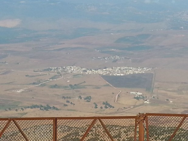 ע׳ג׳ר - ע'ג'ר בצילום מכיוון הר דב. גדר המערכת עוברת בקצה השמאלי של השדה (השטח הכהה) הצמוד לכפר, והמשך הקו הכחול חוצה את הכפר עצמו. צילום: יאיר הנווט