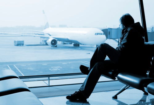man sitting and watching airplane